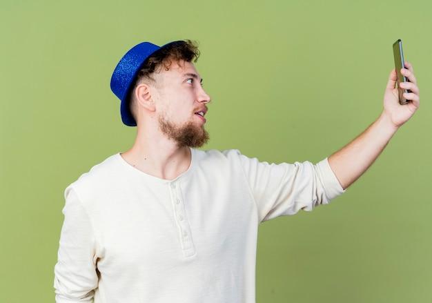 Impressionato giovane ragazzo slavo bello del partito che indossa il cappello del partito che prende selfie isolato su priorità bassa verde oliva