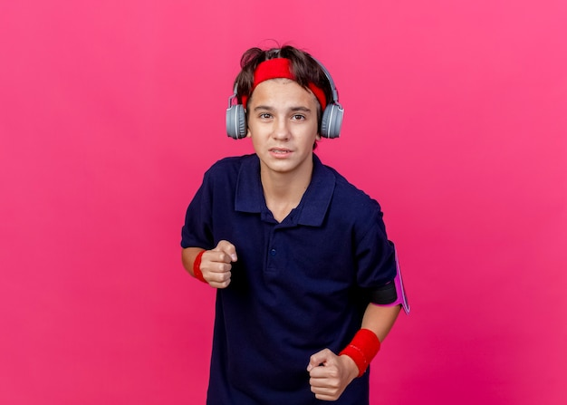 コピースペースのある深紅色の壁に隔離された拳を食いしばる歯列矯正器付きのヘッドバンドとリストバンドとヘッドフォン電話のアームバンドを身に着けている感動した若いハンサムなスポーティな少年