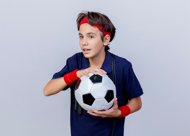 Впечатленный молодой красивый спортивный мальчик, носящий повязку на голову и браслеты с зубными скобами и скакалку на шее, держа футбольный мяч прямо на белом фоне с копией пространства