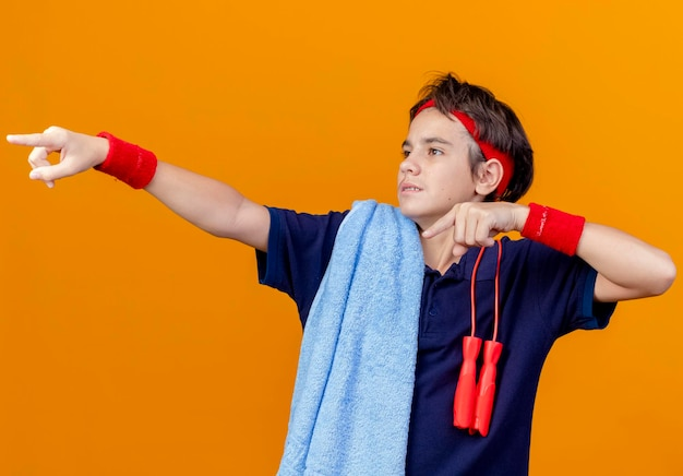 オレンジ色の壁で隔離された側を見て、指している肩に縄跳びが付いている歯科用ブレースとタオルでヘッドバンドとリストバンドを身に着けている感銘を受けた若いハンサムなスポーティな男の子