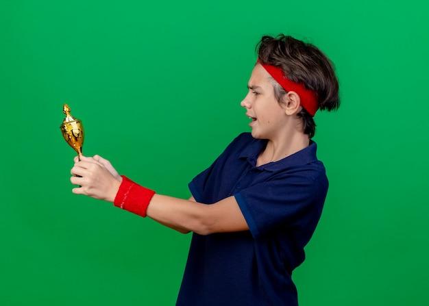 ヘッドバンドとリストバンドを身に着けている印象的な若いハンサムなスポーティな少年は、コピースペースのある緑の壁に隔離された勝者のカップを保持し、見ている歯列矯正器で