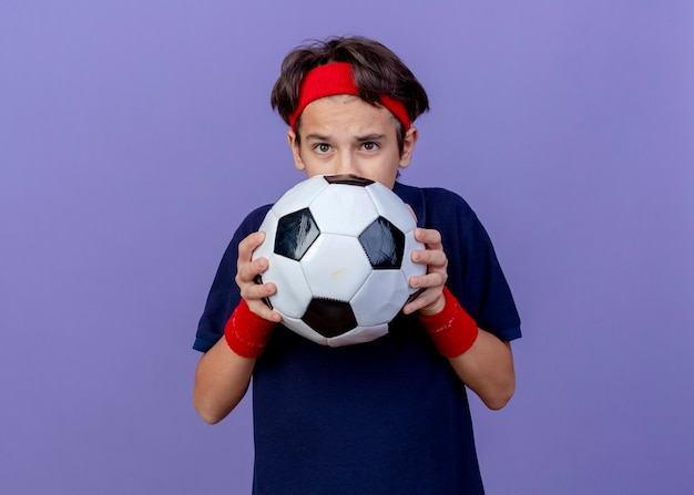 Впечатленный молодой красивый спортивный мальчик с головной повязкой и браслетами с зубными скобами, держащий футбольный мяч сзади, изолированный на фиолетовой стене с копией пространства
