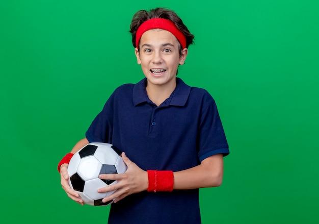 Впечатленный молодой красивый спортивный мальчик с головной повязкой и браслетами с брекетами, держащий футбольный мяч, глядя в камеру, изолированную на зеленом фоне с копией пространства