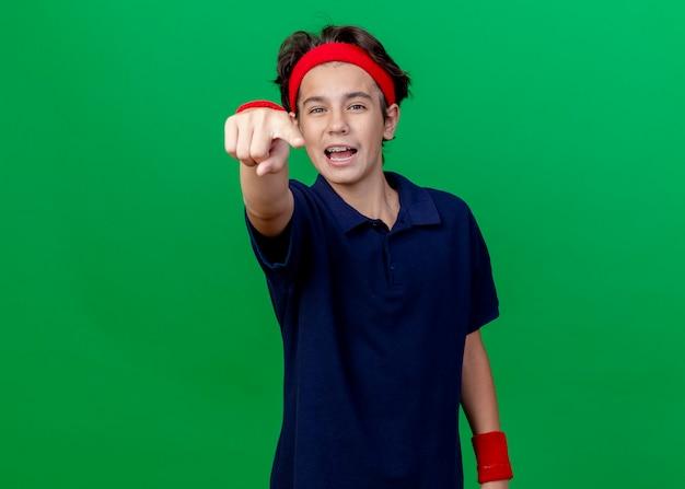 コピースペースで緑の背景に分離されたカメラを見て、指している歯科用ブレース付きのヘッドバンドとリストバンドを身に着けている感動の若いハンサムなスポーティな男の子