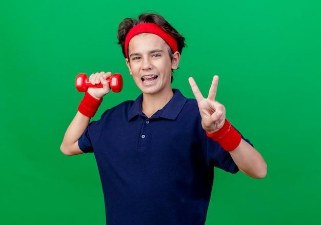 Впечатленный молодой красивый спортивный мальчик с головной повязкой и браслетами с зубными скобами, смотрящий вперед, делающий знак мира, изолированный на зеленой стене