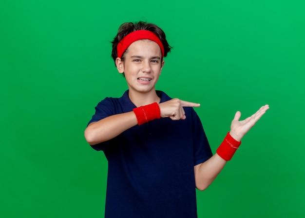 コピースペースで緑の背景に分離されたカメラを見てそれを指している空の手を示す歯科用ブレース付きのヘッドバンドとリストバンドを身に着けている感動の若いハンサムなスポーティな少年