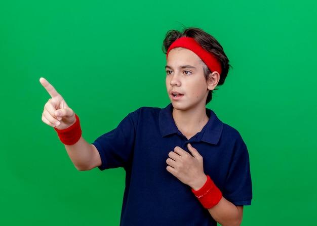 ヘッドバンドとリストバンドを身に着けている印象的な若いハンサムなスポーティな少年は、緑の壁に隔離された胸を見てまっすぐに指している歯列矯正器に触れています