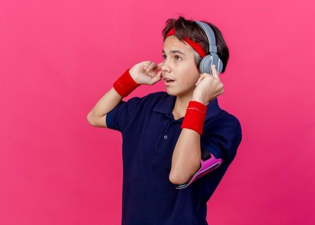 Impressionato giovane ragazzo sportivo bello che indossa la fascia e braccialetti e fascia da braccio del telefono delle cuffie con le parentesi graffe dentali che guardano le cuffie commoventi diritte isolate su fondo cremisi con lo spazio della copia