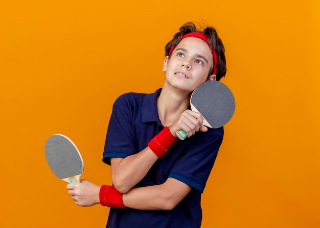 Impressed young handsome sporty boy wearing headband and wristbands with dental braces holding ping pong rackets keeping hands crossed looking up isolated on orange wall
