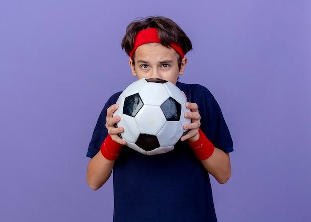 Ha impressionato il giovane ragazzo sportivo bello che indossa la fascia e i braccialetti con le parentesi graffe dentali che tengono il pallone da calcio da dietro isolato sulla parete viola con lo spazio della copia