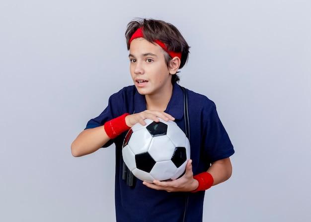 Impressionato giovane ragazzo sportivo bello che indossa fascia e braccialetti con bretelle dentali e corda per saltare intorno al collo tenendo il pallone da calcio guardando dritto isolato su sfondo bianco con spazio di copia