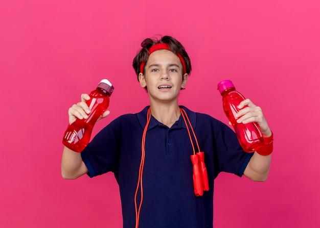 Impressionato giovane ragazzo sportivo bello che indossa fascia e braccialetti con bretelle dentali e corda per saltare intorno al collo tenendo bottiglie d'acqua isolate sulla parete cremisi