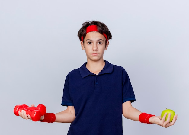 Impressed young handsome sporty boy wearing headband and wristbands with dental braces looking at camera holding dumbbells and apple isolated on white background