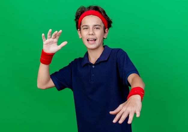 Impressionato giovane ragazzo sportivo bello che indossa la fascia e braccialetti con bretelle dentali che guarda l'obbiettivo tenendo le mani in aria isolato su sfondo verde con spazio di copia