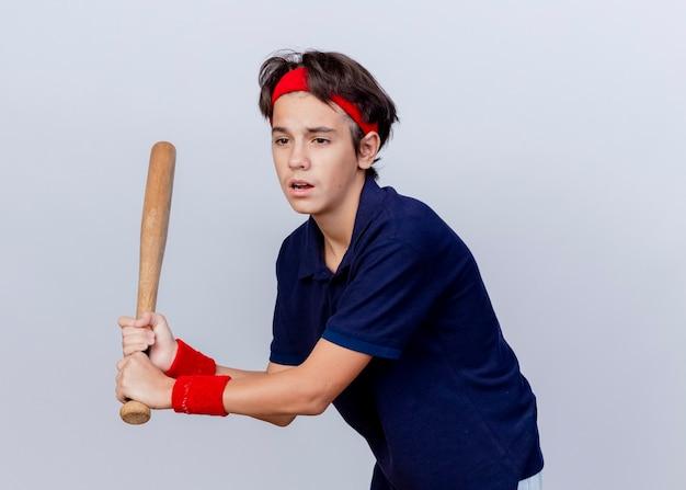 Impressionato giovane ragazzo sportivo bello che indossa la fascia e braccialetti con bretelle dentali guardando il lato che tiene la mazza da baseball che gioca baseball isolato su priorità bassa bianca con lo spazio della copia