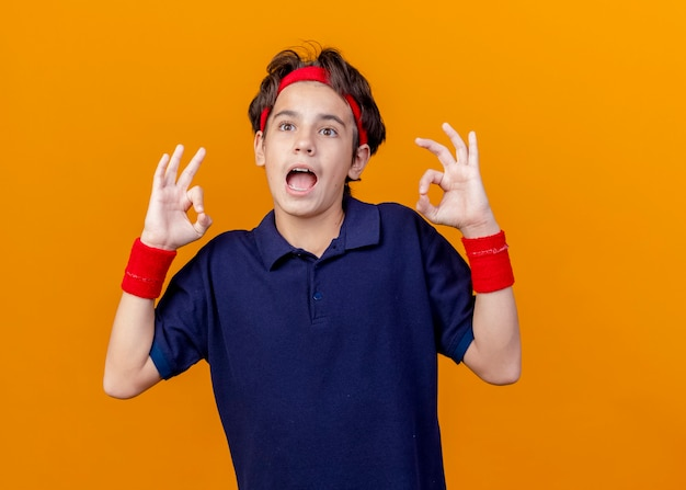 Ha impressionato il giovane ragazzo sportivo bello che indossa la fascia e i braccialetti con le parentesi graffe dentali che guardano diritto facendo segno giusto isolato sulla parete arancione con lo spazio della copia