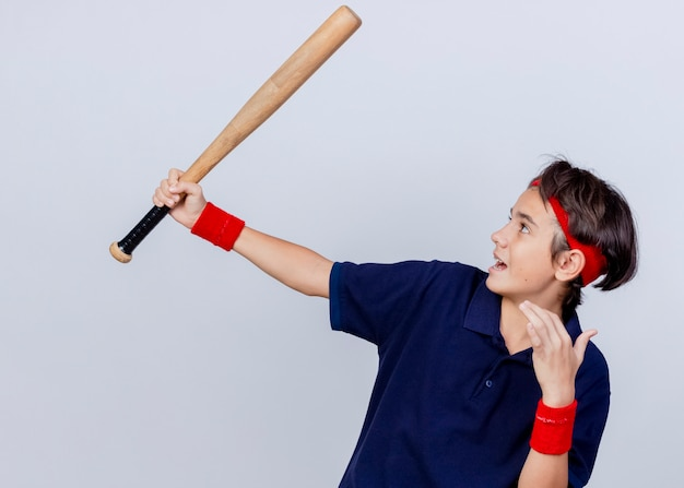 Impressed young handsome sporty boy wearing headband and wristbands with dental braces raising up baseball bat looking at it keeping hand in air isolated on white background