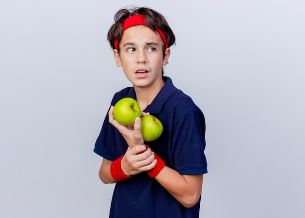 Impressed young handsome sporty boy wearing headband and wristbands with dental braces standing in profile view holding apples and wrist looking at side isolated on white background with copy space