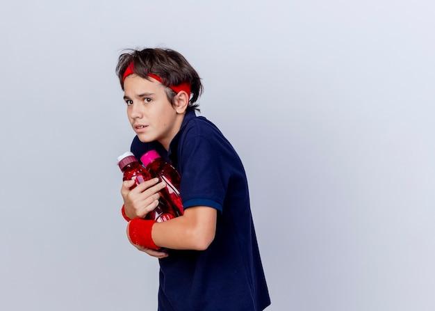 Impressionato giovane ragazzo sportivo bello che indossa la fascia e braccialetti con bretelle dentali in piedi nella vista di profilo tenendo le bottiglie d'acqua guardando il lato isolato su sfondo bianco con lo spazio della copia