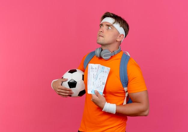 Впечатленный молодой красивый спортивный мужчина с повязкой на голову, браслетами и задней сумкой с наушниками на шее, держащий билеты на самолет и футбольный мяч, выглядящий прямо