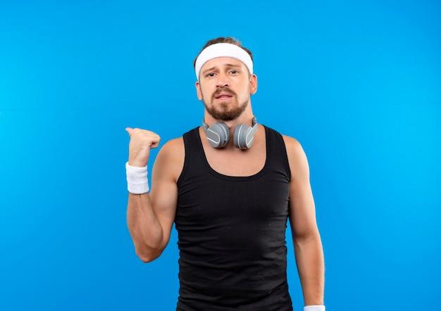 파란색 벽에 고립 된 뒤에 가리키는 목 주위에 머리띠와 팔찌와 헤드폰을 착용하는 감동 젊은 잘 생긴 스포티 한 남자