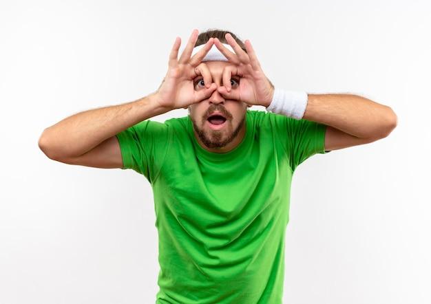 白い壁に分離された双眼鏡として手を使って、ヘッドバンドと表情のジェスチャーをしているリストバンドを身に着けている印象的な若いハンサムなスポーティな男