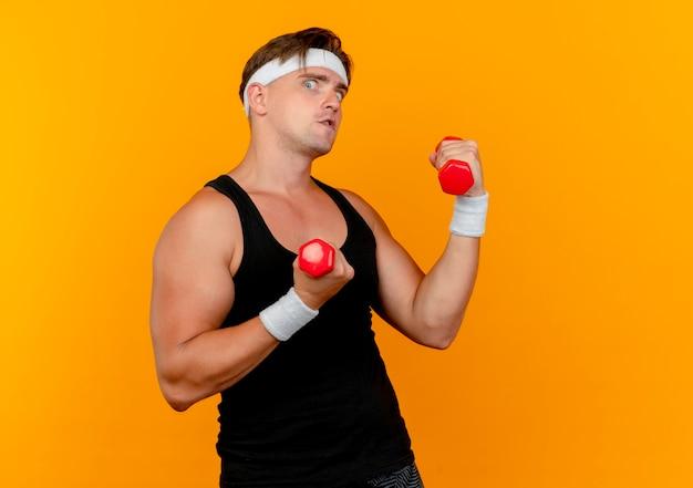 Впечатленный молодой красивый спортивный мужчина с повязкой на голову и браслетами с гантелями, изолированными на оранжевом