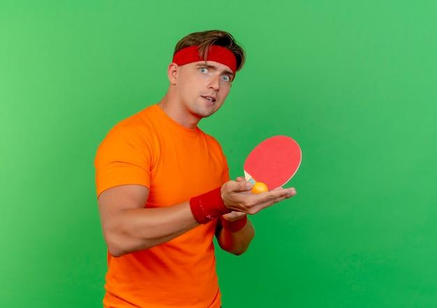 Впечатленный молодой красивый спортивный мужчина с головной повязкой и браслетами, держащий ракетку для пинг-понга и мяч, изолированные на зеленом
