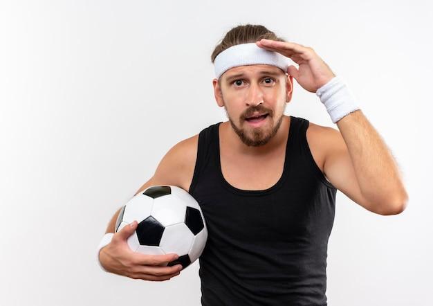 Впечатленный молодой красивый спортивный мужчина с головной повязкой и браслетами держит футбольный мяч и кладет руку возле лба, изолированного на белой стене