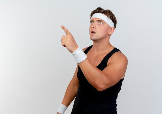 Впечатленный молодой красивый спортивный мужчина с головной повязкой и браслетами смотрит и указывает прямо на белом