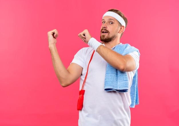 Впечатленный молодой красивый спортивный мужчина с головной повязкой и браслетами, указывающими сзади со скакалкой и полотенцем на плечах, изолированном на розовой стене