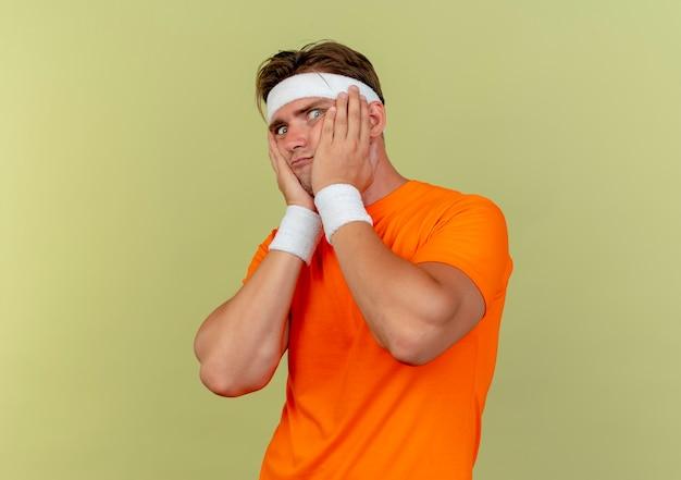 Впечатленный молодой красивый спортивный мужчина с повязкой на голову и браслетами, положив руки на щеки, изолированные на оливково-зеленом