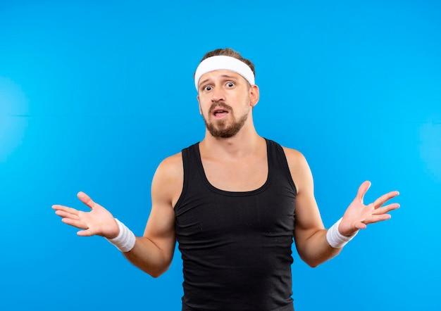 Впечатленный молодой красивый спортивный мужчина с головной повязкой и браслетами, показывающий пустые руки, изолированные на синей стене