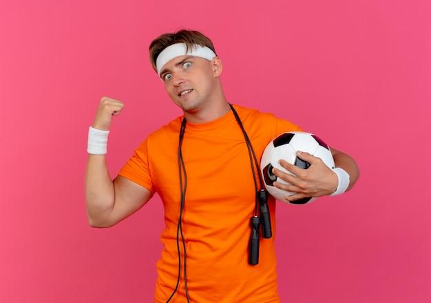Впечатленный молодой красивый спортивный мужчина с головной повязкой и браслетами со скакалкой на шее, держащий футбольный мяч, указывающий позади изолированного на розовом