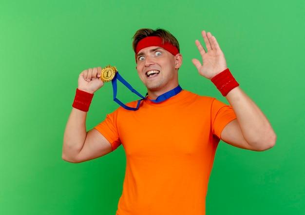 ヘッドバンドとリストバンドを身に着けている印象的な若いハンサムなスポーティな男は、メダルを保持し、緑で隔離の手を上げて首の周りにメダルを持っています