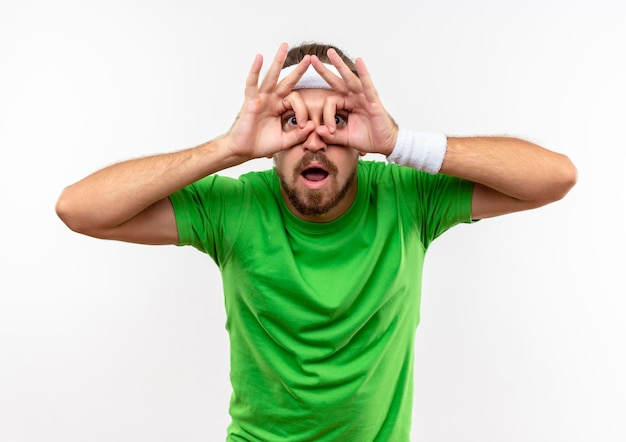 Impressed young handsome sporty man wearing headband and wristbands doing look gesture using hands as binoculars isolated on white wall