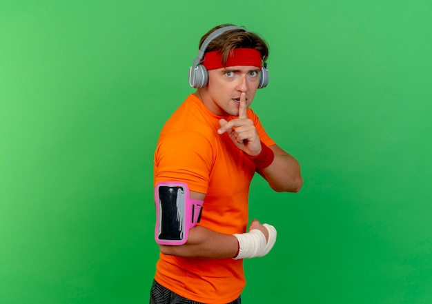 Impressed young handsome sporty man wearing headband and wristbands and headphones and phone armband with wrist wrapped with bandage standing in profile view gesturing silence