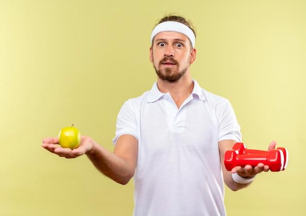 Impressionato giovane uomo sportivo bello che indossa fascia e braccialetti che tengono mela e manubri isolati sul muro verde