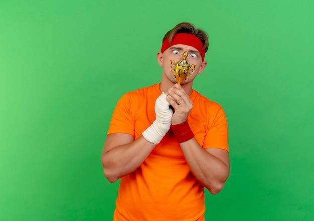 Impressionato giovane uomo sportivo bello che indossa fascia e braccialetti tenendo e guardando la coppa del vincitore con polso ferito avvolto con benda isolato su verde