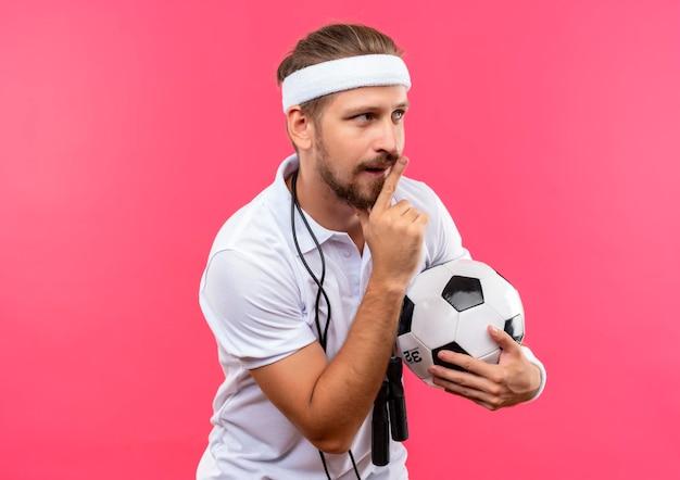 Impressionato giovane bell'uomo sportivo che indossa fascia e braccialetti che tengono il pallone da calcio gesticolando silenzio e guardando di lato con la corda per saltare intorno al collo isolato sul muro rosa
