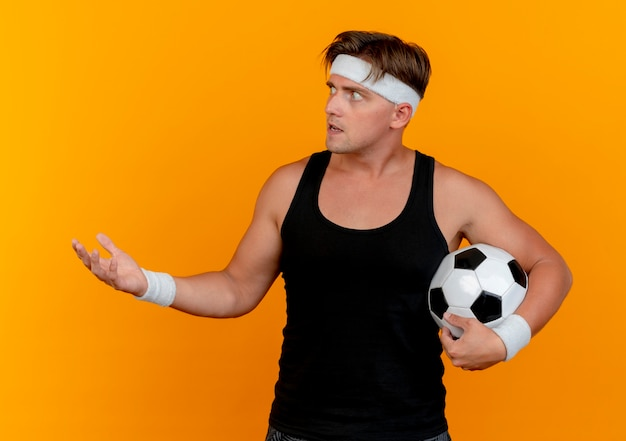 Impressed young handsome sporty man wearing headband and wristbands holding soccer ball looking at side and showing empty hand isolated on orange