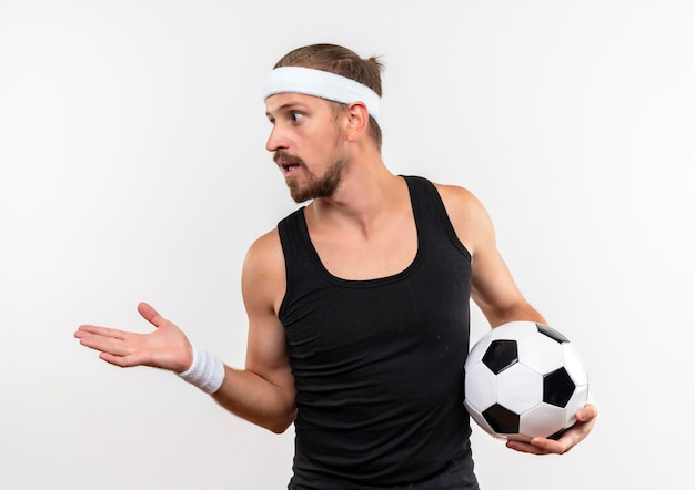 Impressed young handsome sporty man wearing headband and wristbands holding soccer ball looking at side showing empty hand isolated on white wall