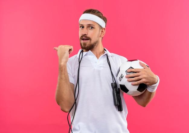 Impressionato giovane uomo sportivo bello che indossa fascia e braccialetti che tengono il pallone da calcio che punta dietro e con la corda per saltare intorno al collo isolato sul muro rosa