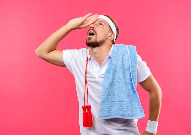 Impressionato giovane uomo sportivo bello che indossa fascia e braccialetti mettendo la mano sulla fronte e guardando in alto con asciugamano e corda per saltare sulle spalle isolato sul muro rosa