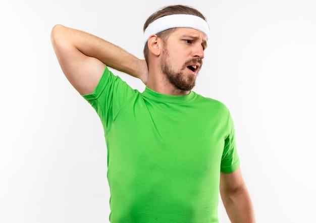 Impressionato giovane uomo sportivo bello che indossa fascia e braccialetti mettendo la mano sul collo guardando il lato isolato sul muro bianco