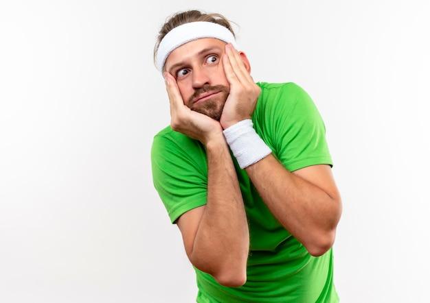 Impressionato giovane uomo sportivo bello che indossa fascia e braccialetti mettendo le mani sul viso guardando il lato isolato sul muro bianco con spazio di copia