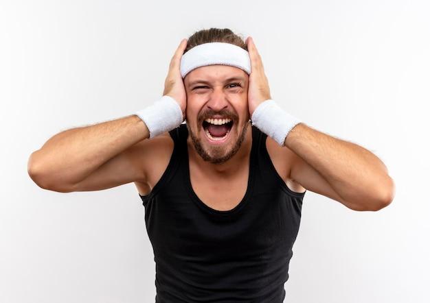 Impressionato giovane uomo sportivo bello che indossa fascia e braccialetti mettendo le mani sulla testa isolata sul muro bianco