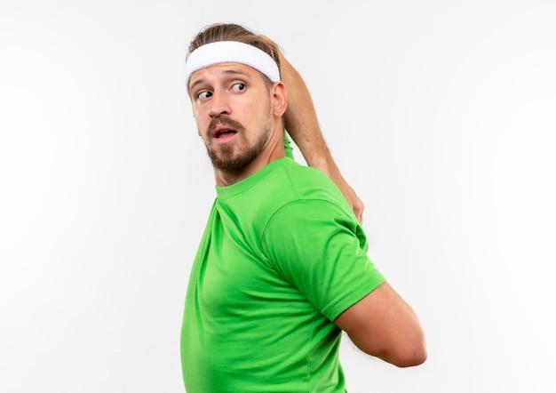Impressionato giovane bell'uomo sportivo che indossa fascia e braccialetti in piedi in vista di profilo mettendo insieme le mani dietro la schiena e guardando dietro isolato sul muro bianco con spazio di copia