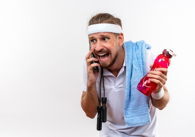Impressionato giovane bell'uomo sportivo che indossa fascia e braccialetti parlando al telefono tenendo una bottiglia d'acqua con asciugamano e corda per saltare sulle spalle isolato sul muro bianco con spazio copia