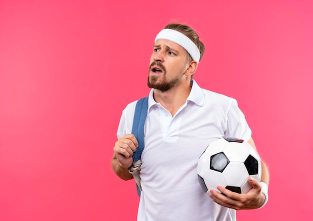 Impressed young handsome sporty man wearing headband and wristbands with back bag on shoulder holding soccer ball looking at side isolated on pink wall with copy space